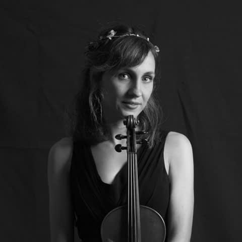 Headshot of Irene Senent wearing a flower crown with a violin